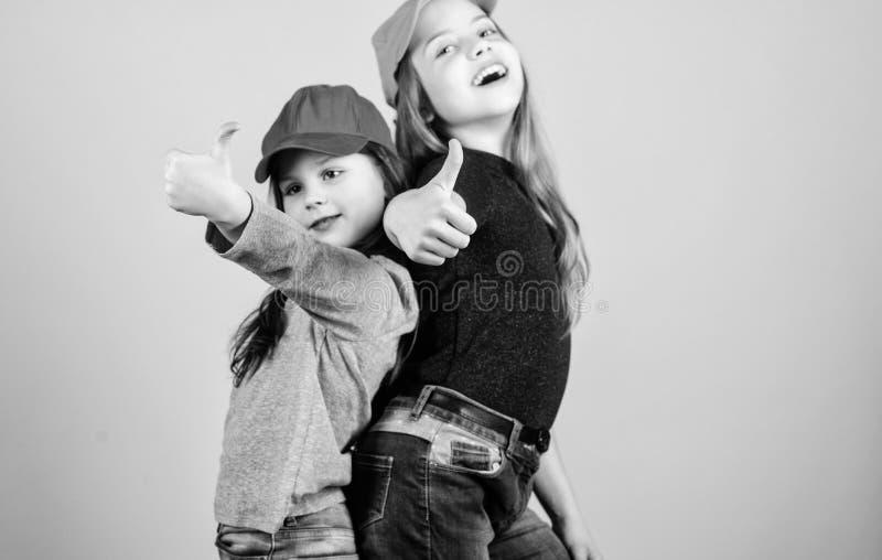 Cool girls. Little cute girls wearing bright baseball caps. Modern fashion. Stylish accessory. Kids fashion. Feeling. Confident wearing caps. Sisters stand back royalty free stock photo