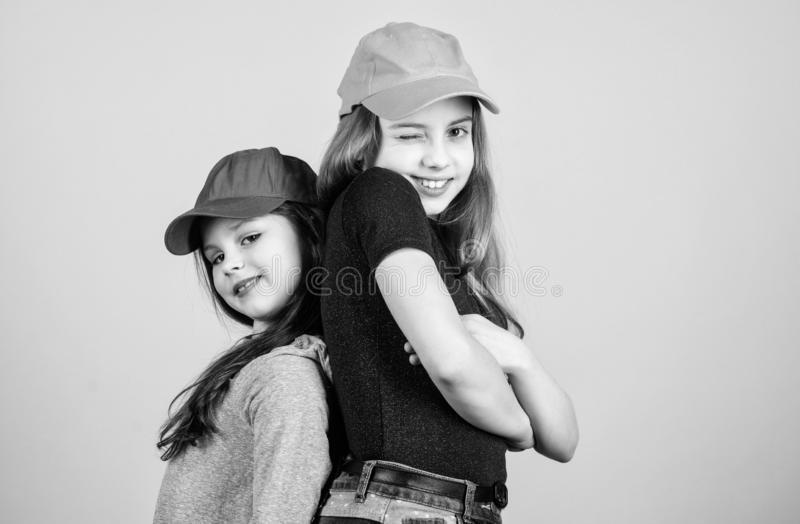 Cool girls. Sisters stand back to back beige background. Little cute girls wearing bright baseball caps. Modern fashion. Hats and caps. Stylish accessory. Kids stock images