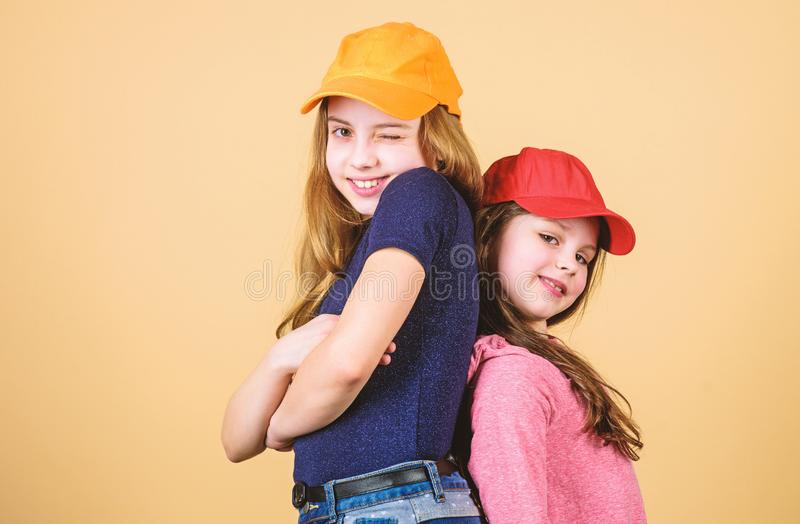 Cool girls. Sisters stand back to back beige background. Little cute girls wearing bright baseball caps. Modern fashion. Hats and caps. Stylish accessory. Kids stock photography