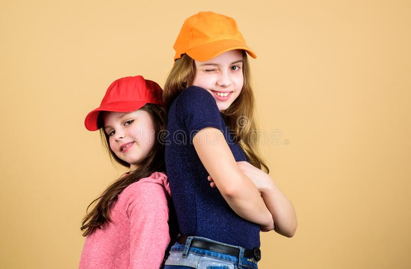 Cool girls. Sisters stand back to back beige background. Little cute girls wearing bright baseball caps. Modern fashion royalty free stock photos