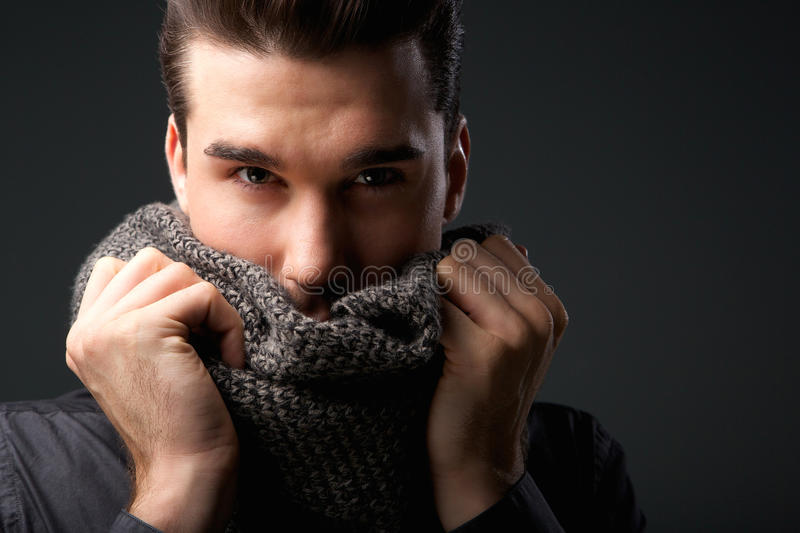 Cool guy holding grey wool scarf over face. Close up portrait of a cool guy holding grey wool scarf over face stock image