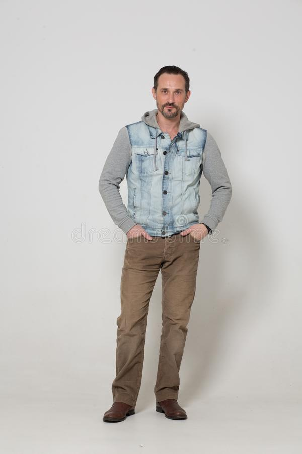 Portrait of fashion dressed man. Cool guy in jeans sleeveless jacket and brown trousers. men concept royalty free stock photo