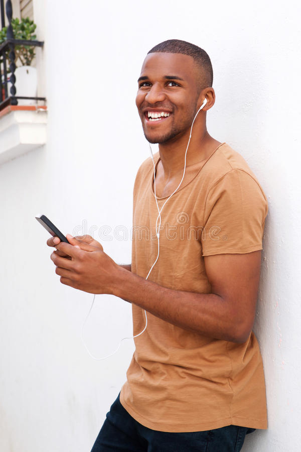 Free Cool Guy Standing Outside With Mobile Phone And Earphones Listening To Music Stock Photography - 96739202