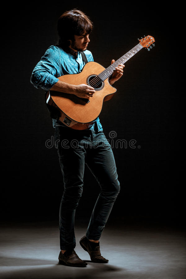 Free Cool Guy Standing With Guitar On Dark Background Royalty Free Stock Images - 85238949