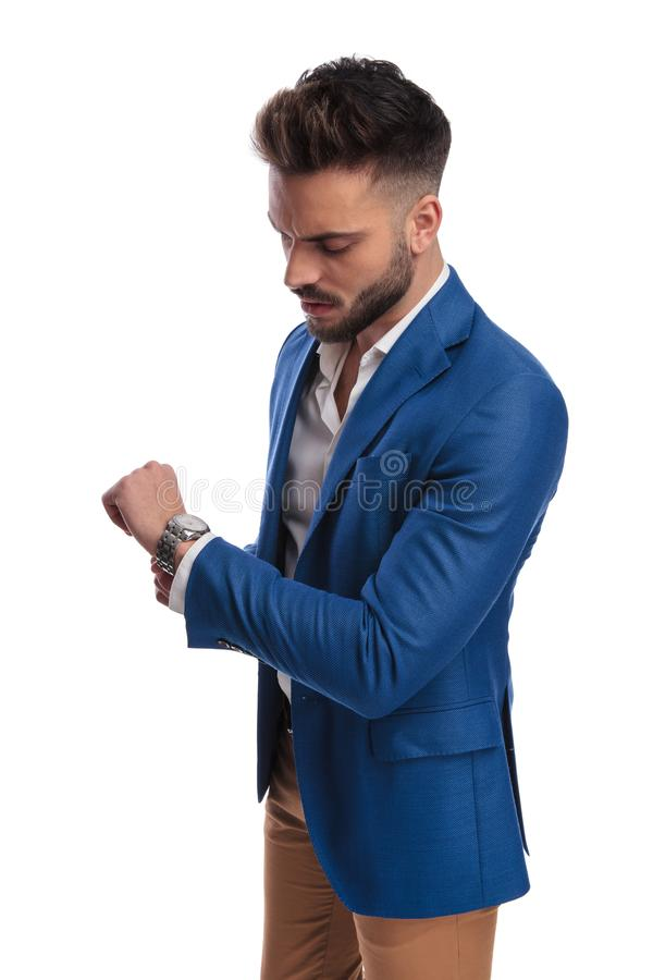 Cool guy in suit checking time on his watch stock photo