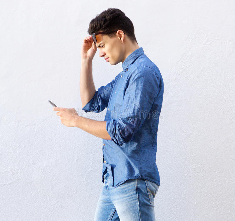 Cool guy walking and looking at mobile phone royalty free stock photography