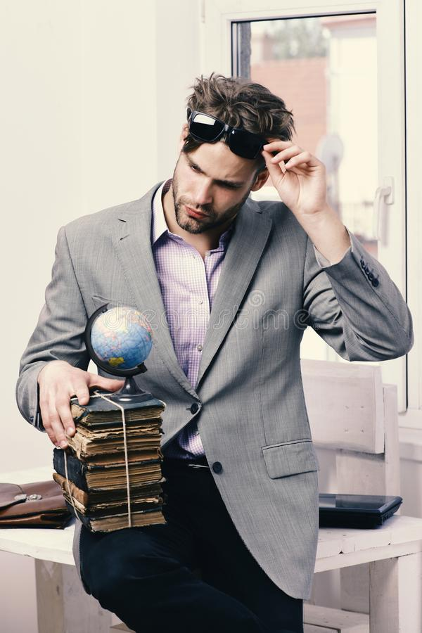Cool guy wears grey suit. Business and knowledge concept. Businessman with pile of old books royalty free stock photo