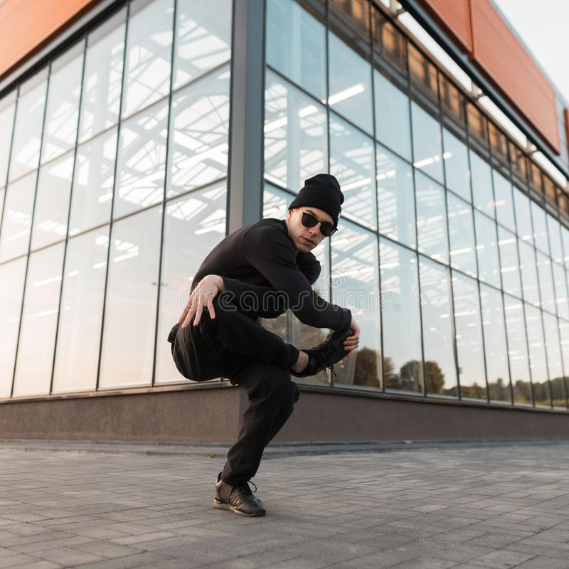 Cool handsome young hipster man dancer in knitted hat in stylish black clothes in trendy sunglasses dancing break dance. In the city near the glass building royalty free stock images