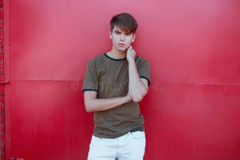 Cool handsome young man with a stylish hairstyle in a trendy green t-shirt in white trousers near the bright pink metal wall. On a warm summer day. Attractive royalty free stock photography