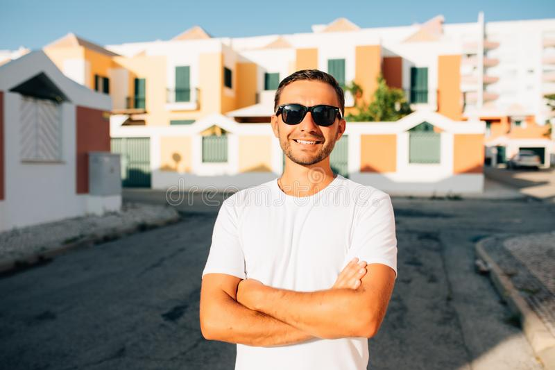 Cool and handsome. Handsome young man in sunglasses keeping arms crossed and looking away while standing on the summer street stock photo
