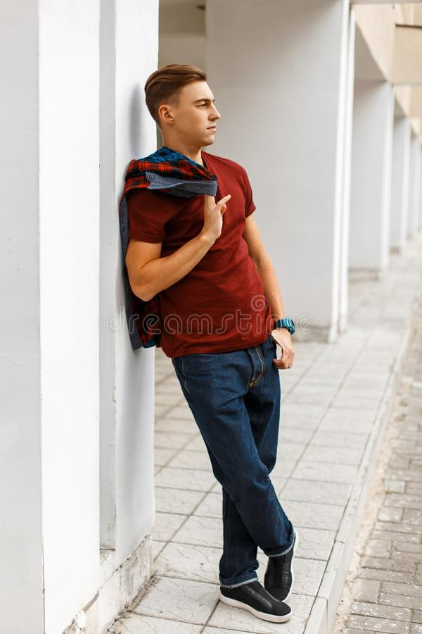 Cool handsome young man in trendy red t-shirt in a plaid fashionable shirt in blue jeans in sneakers posing on the street royalty free stock photography