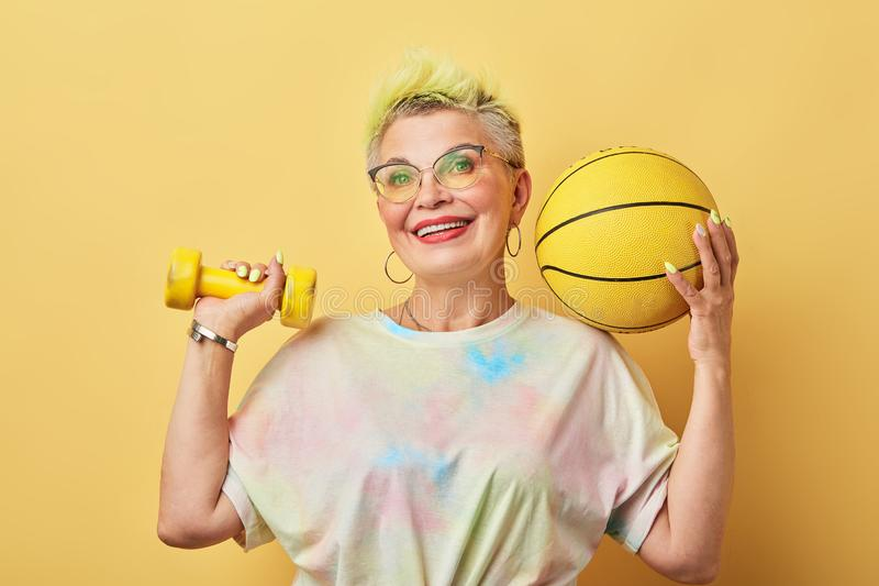Cool happy senior woman with dumbbells and ball posing to the camera stock photo