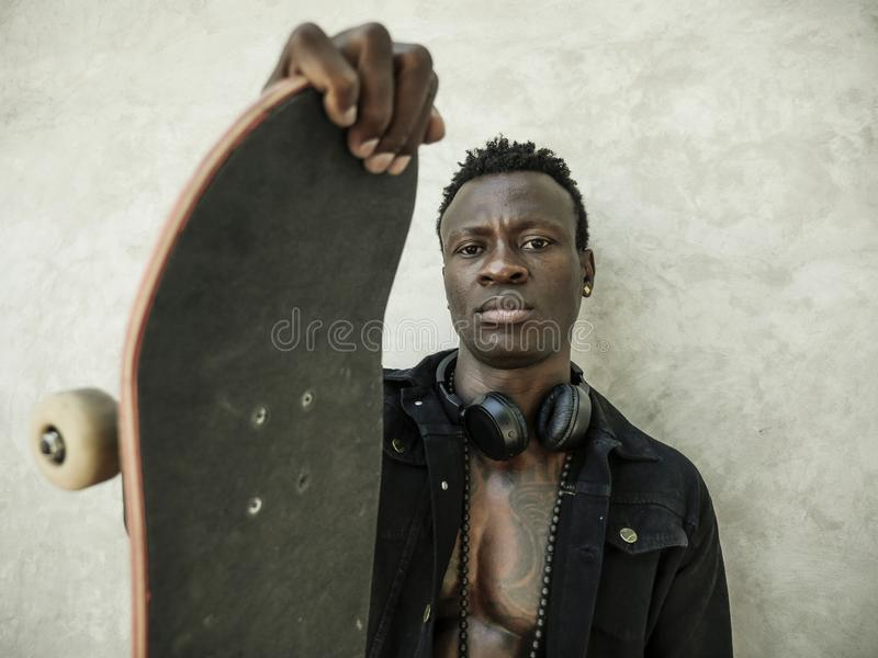 Cool isolated portrait of young attractive and confident hipster black afro American man leaning on street wall holding skate royalty free stock photos
