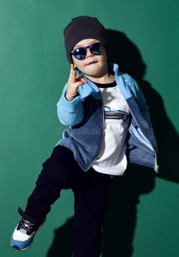 Cool kid boy in blue sunglasses, headwear, fleece jacket, pants and sneakers is dancing, showing cool sing on green. Cool kid boy in blue sunglasses, headwear royalty free stock photos