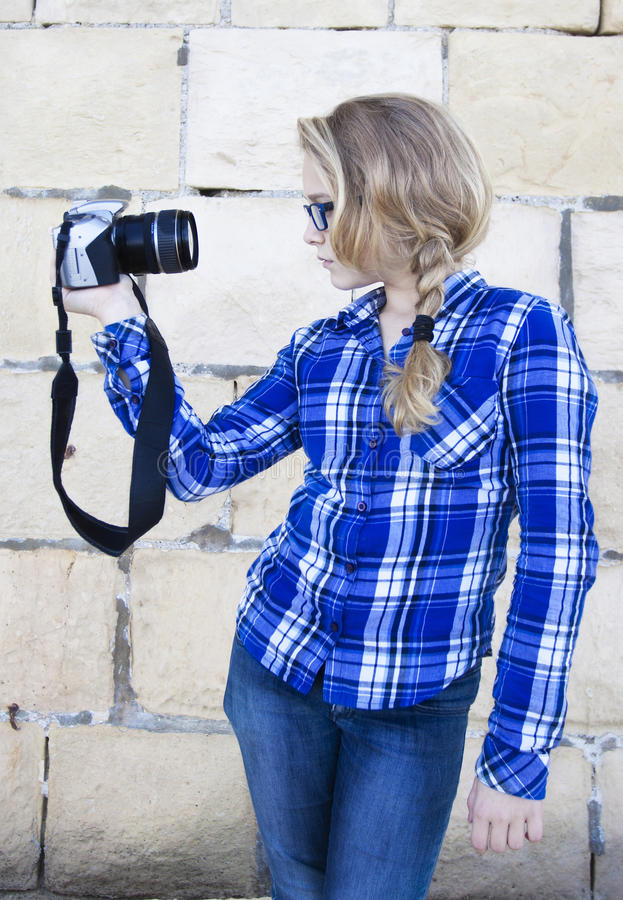 Cool kid holding a camera taking a photo of herself stock photo