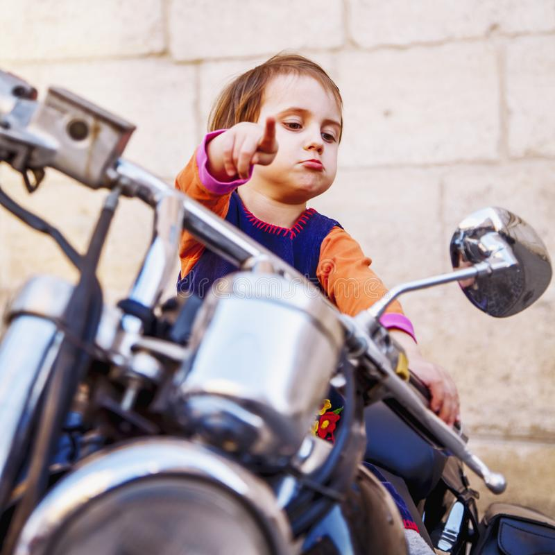 Cool little biker girl playing and having fun on fashioned motorcycle. Humorous portrait of child points to the road with finger royalty free stock photography