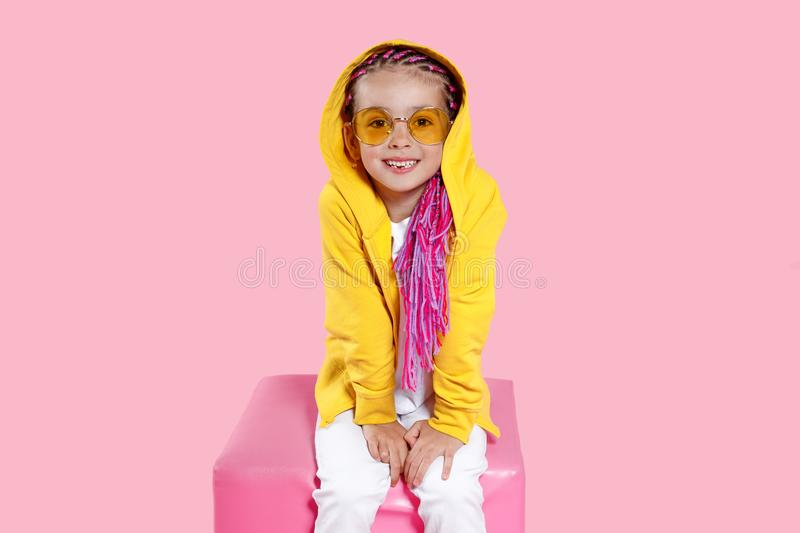 Cool little child wearing in white jeans, yellow sunglasses colored clothes sitting in the studio, over pink background. royalty free stock images