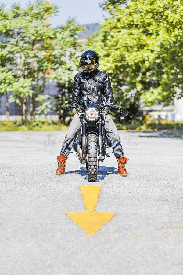 Cool looking motorcycle rider on custom made scrambler style cafe racer on the road with an arrow sign stock photos