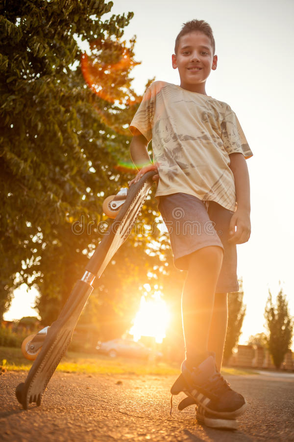 Cool looking skater boy on sunset. Happy smiling boy with skateboard stock photo