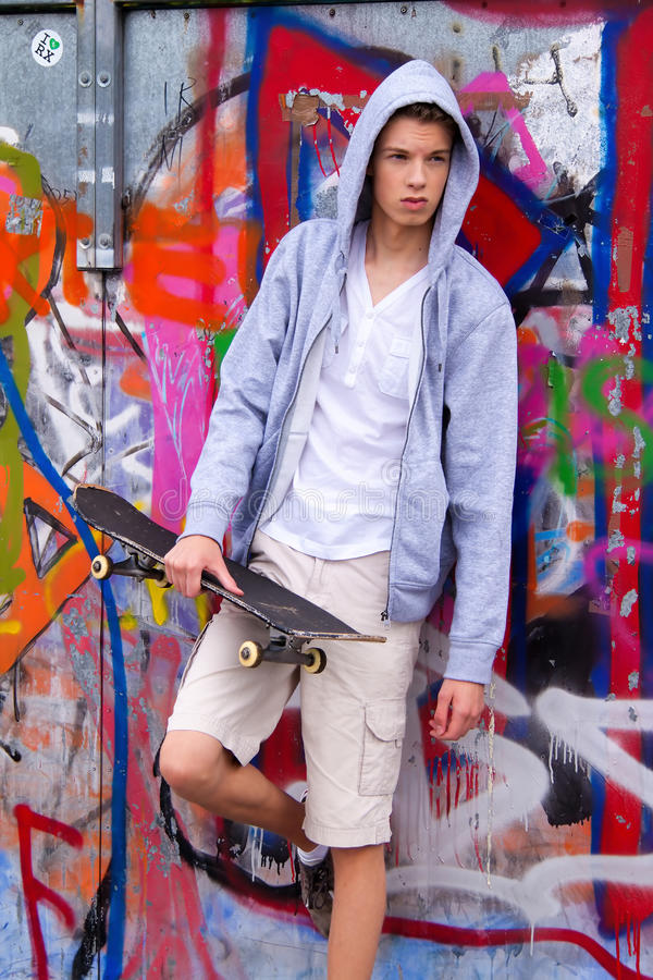 Cool-looking young man in front of graffiti stock photos
