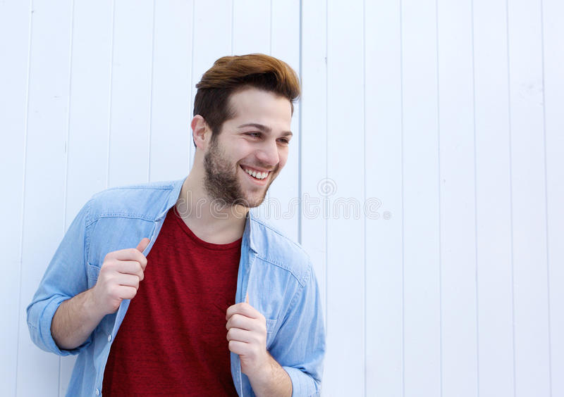 Cool male fashion model smiling against white background stock photo