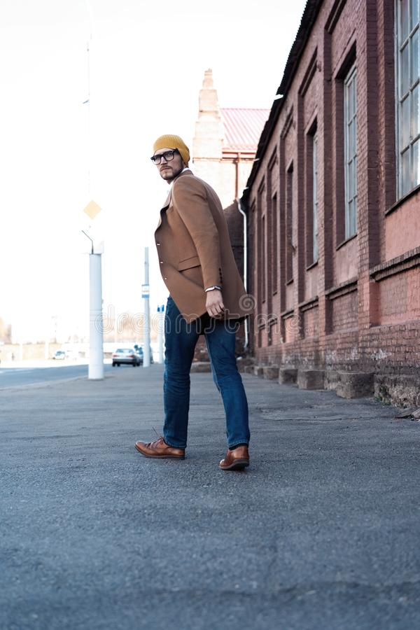 Cool man beautiful model outdoors, city style fashion. A handsome man model walking in the city center. Urban setting royalty free stock photo
