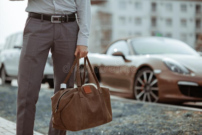 Cool man beautiful model outdoors, city style fashion. A handsome man model walking in the city center next to some cars. Urban setting. The young boy as stock photography