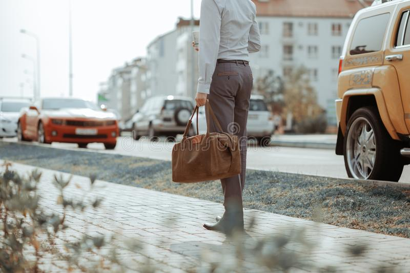 Cool man beautiful model outdoors, city style fashion. A handsome man model walking in the city center next to some cars. Urban setting. The young boy as stock photo