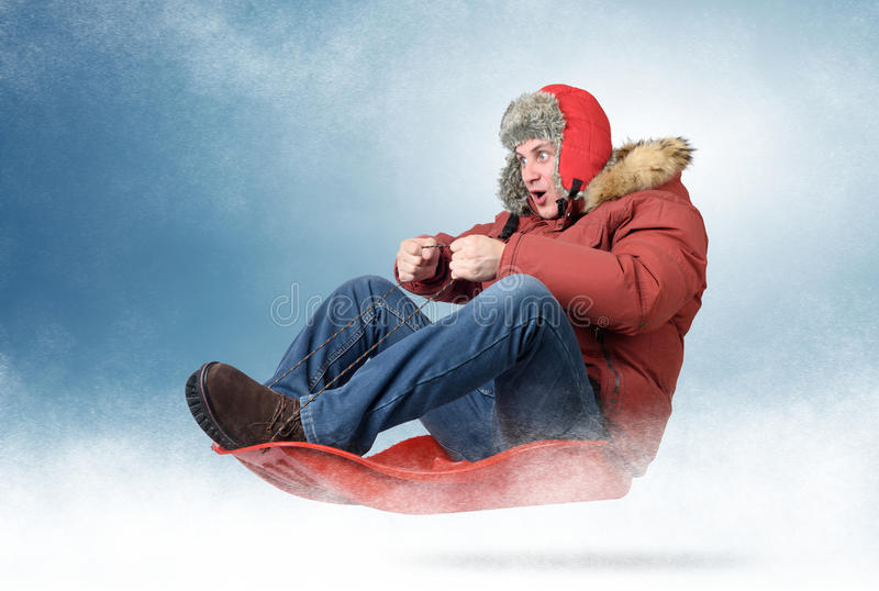 Cool man fly on a sled in the snow. Concept winter driving royalty free stock photos
