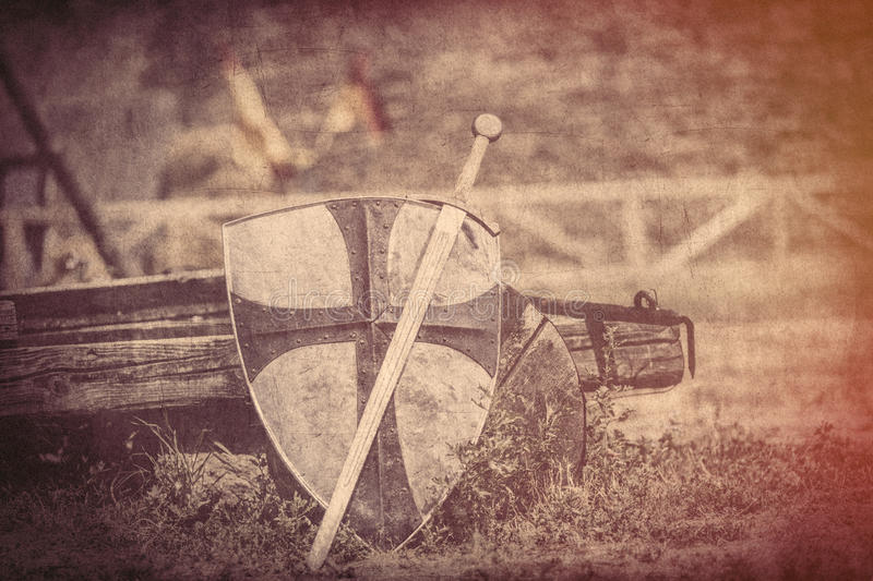 Cool metallic sword and heavy shield on the middle ages wagon ba. Ckground stock images