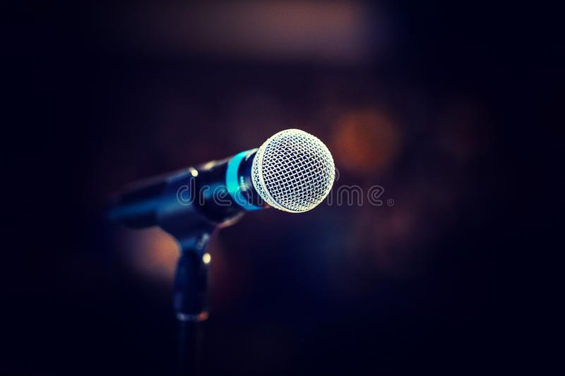 Cool mic on a stand in front of the concert hall, beautiful blurred dark background with a copy space for a message. Cool mic on a stand in front of the royalty free stock image