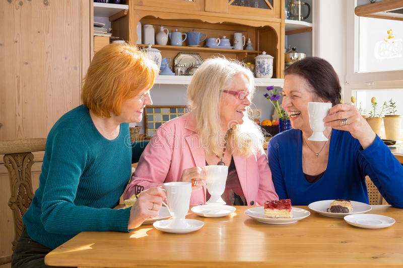 Cool Middle Age Female Friends Having Snacks. Three Cool Middle Age Female Friends Having Snacks at the Cafe While Talking Something Interesting stock photography