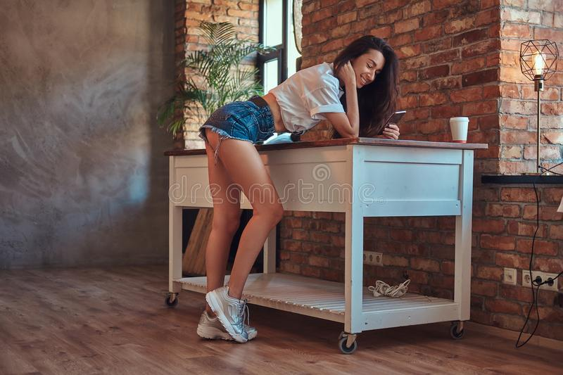 Cool modern brunette girl wearing a white top and denim shorts standing leaning on a table while using a smartphone in royalty free stock photos