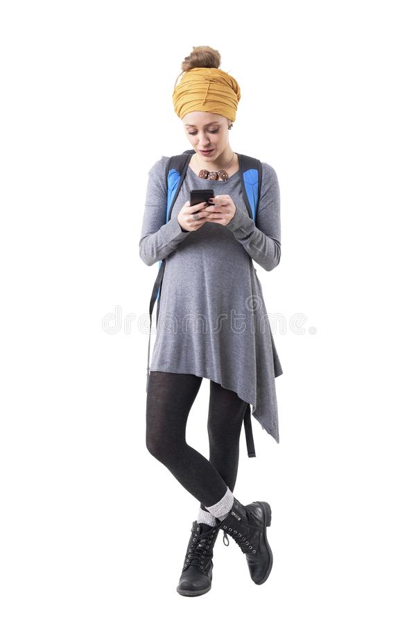 Cool modern stylish hipster traveler woman with rucksack reading messages on cellphone. royalty free stock images