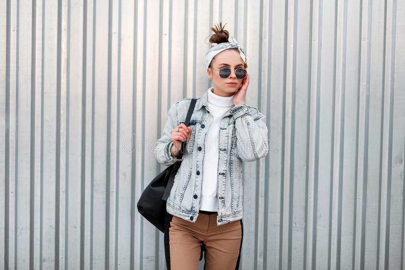 Cool modern young hipster woman in a bandana in a summer denim jacket in a knitted white vintage sweater in beige pants. With a black handbag in sunglasses near royalty free stock images
