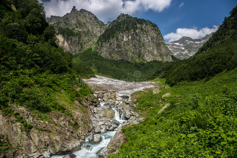 Cool mountain stream flowing from under the glacier. Highland pass royalty free stock images