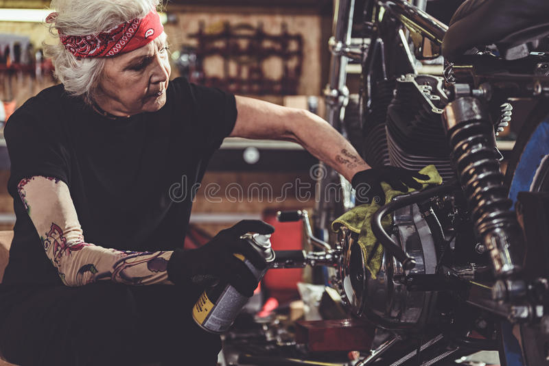 Cool pensioner burnishing bike in mechanic shop. Serene old woman keeping duster and rubbing motorcycle in garage stock image