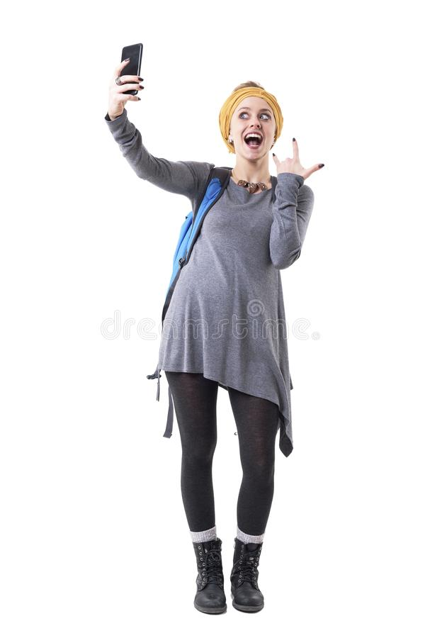 Cool playful excited young backpacker woman taking selfie with rock n roll gesture. royalty free stock photo