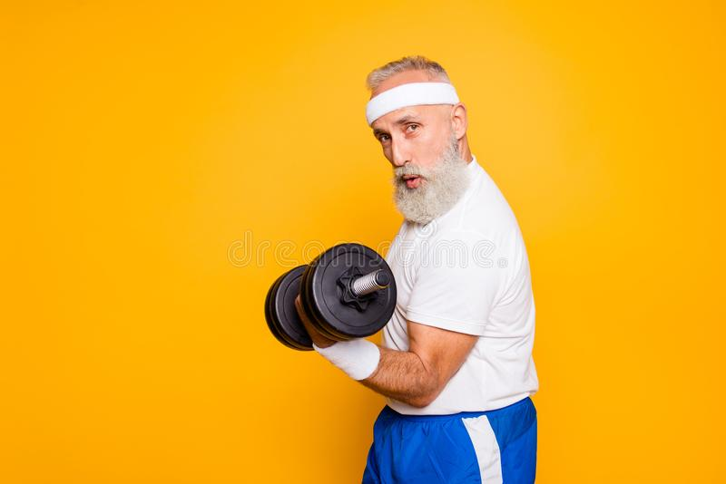 Cool playful flirty naughty strong grandpa with confident grimace exercising holding equipment up, lifts it with strength and pow royalty free stock images