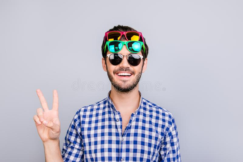 Cool! Playful young brunette bearded man in three pairs of bright colorful glasses and checkered casual shirt is fooling around, p royalty free stock images