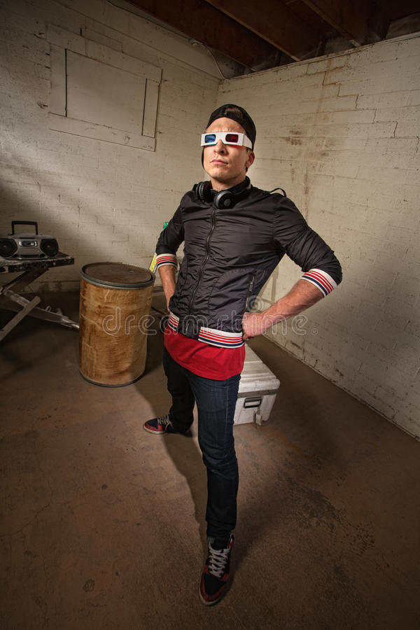Cool Rapper in Basement. Posing Caucasian rapper in basement with hands on hips royalty free stock images