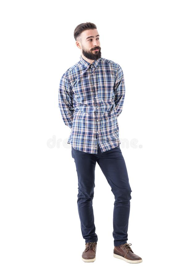 Cool relaxed flirty bearded man with hands behind back judging and looking away royalty free stock image