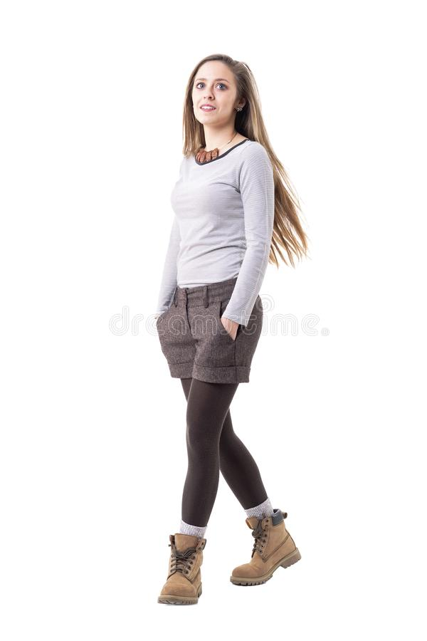 Cool relaxed young millennial hipster girl in retro clothes walking with hands in pockets. stock photos