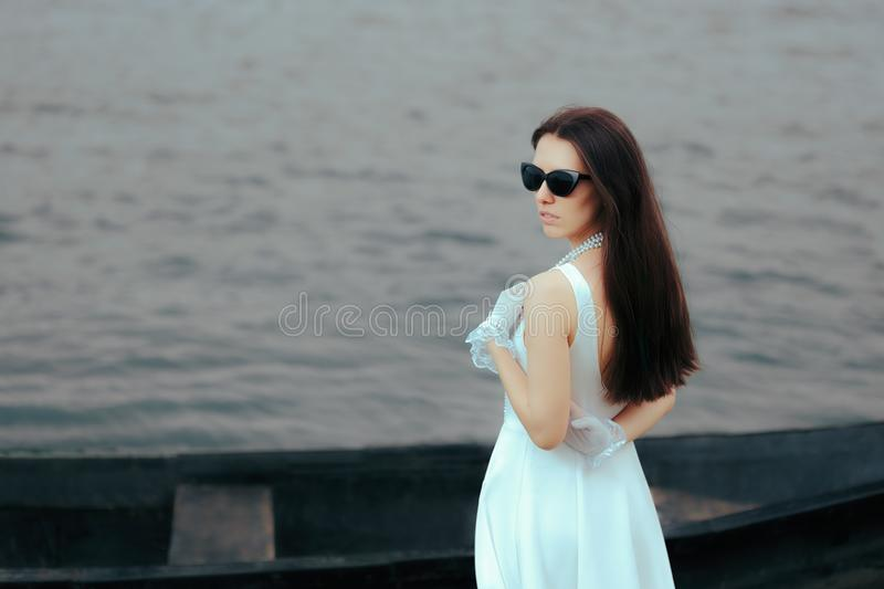 Fashionable Vintage Girl with Cat-eye Sunglasses and Lace Gloves. Cool retro diva posing outdoors near watercraft stock images