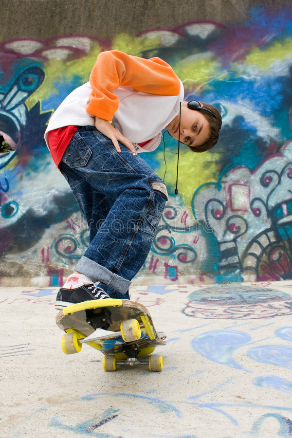 Cool skater against a graffiti wall royalty free stock images