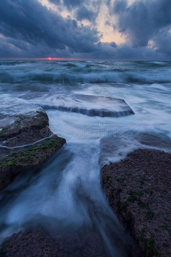 Cool stormy beach sunset  with sun royalty free stock image