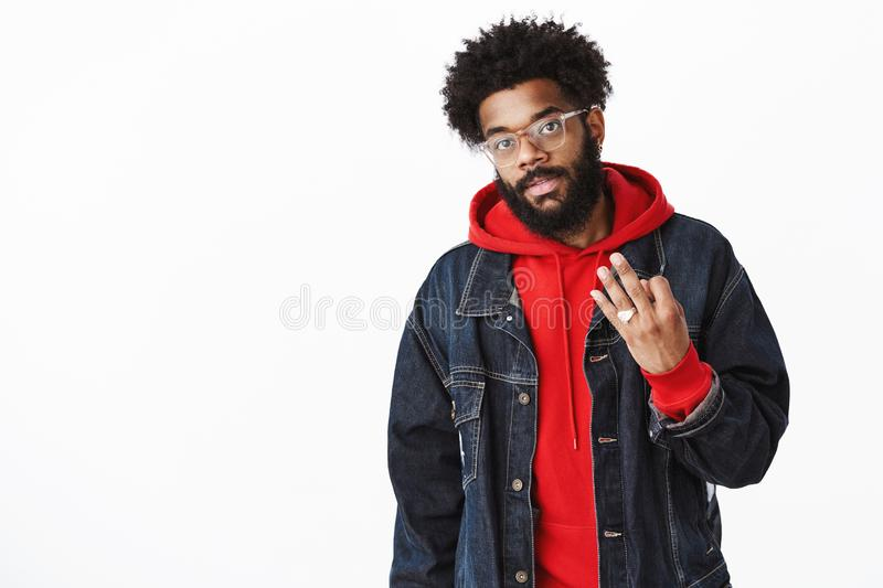 Cool and stylish urban african american guy in glasses, rings and denim jacket over hoodie with pierced nose and afro stock photography