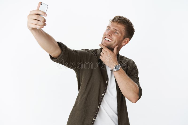 Cool and stylish young handsome blond man touching chin and smiling broadly as extending hand to take selfie on stock photo