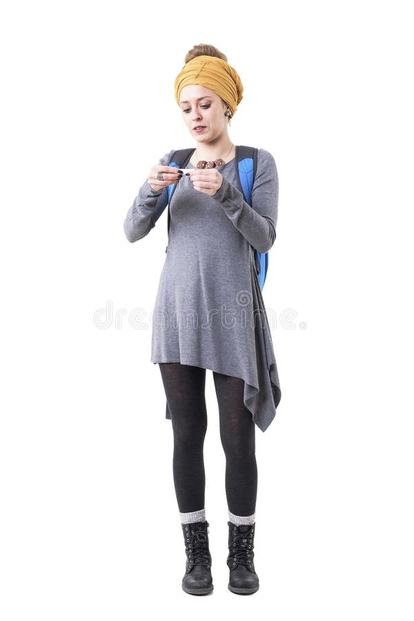 Cool stylish young hipster tourist woman rolling tobacco cigarettes carrying backpack. royalty free stock images