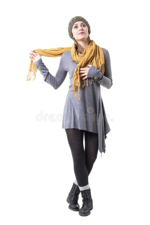 Cool stylish young woman in warm clothing wrapping scarf around neck. stock photography